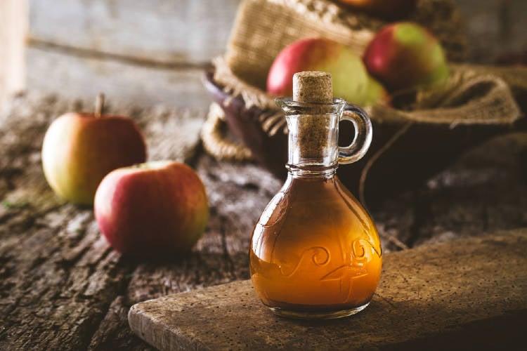 Una botella de vinagre con manzanas de fondo
