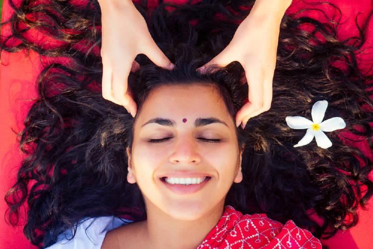 Una mujer recibiendo un masaje capilar