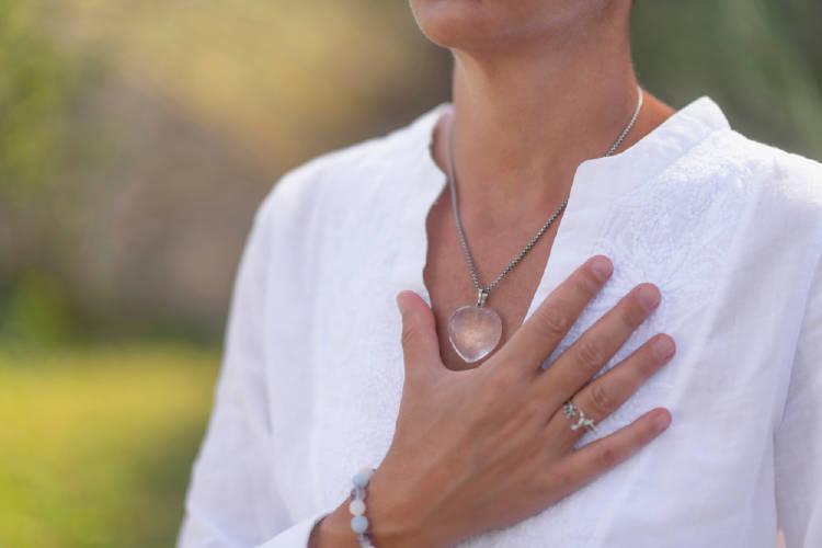 mujer de blanco con una mano en el corazon