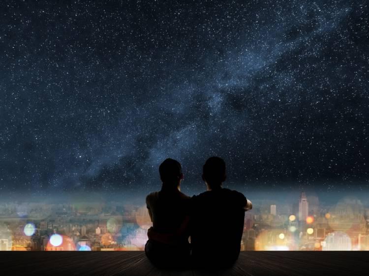 Una pareja se abraza mientras mira el cielo estrellado
