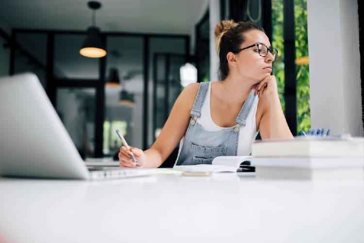 Una mujer se distrae mientras estudia