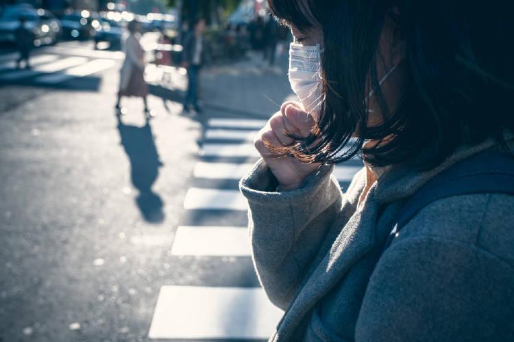 Una mujer con barbijo tose en la calle