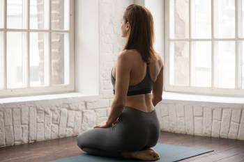 Una mujer practica la postura de yoga del diamante