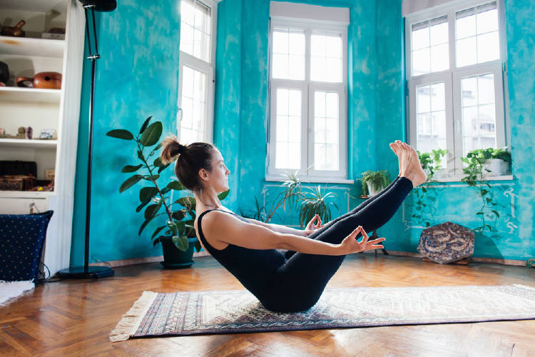 Una mujer practica yoga en la postura del barco