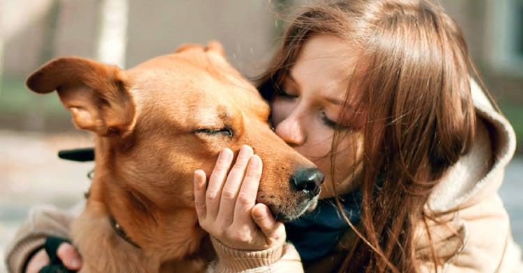 chica besando a su perro en la calle
