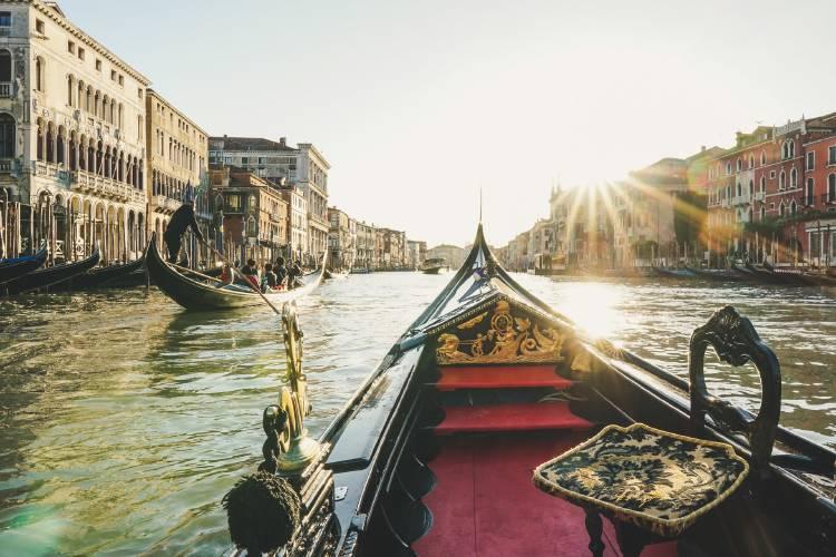 góndola en canal de Venecia con rayos de sol reflejándose en el agua