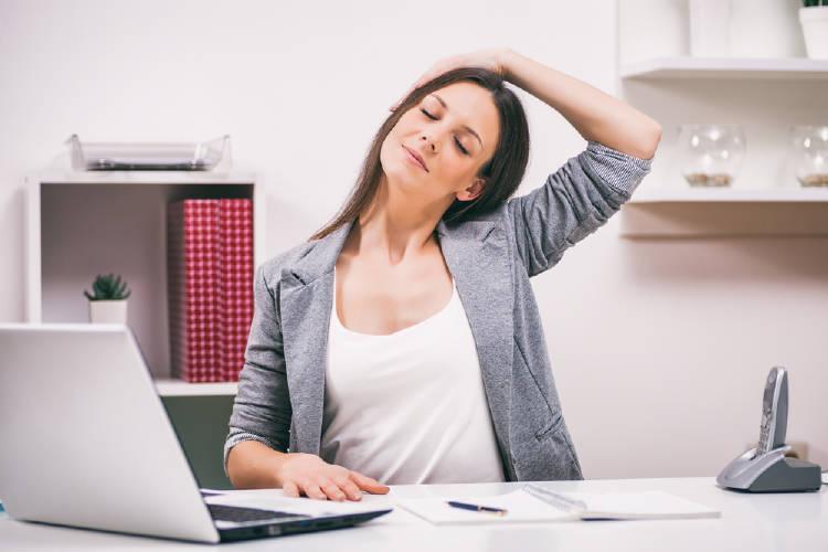 mujer estira cuello cervicales en computadora oficina