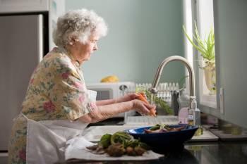 Mujer mayor en la cocina lavando verduras