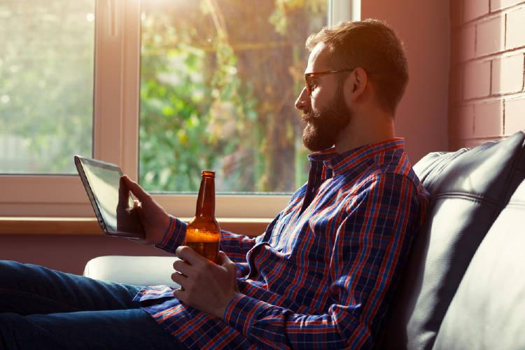 hombre bebe cerveza y mira tablet