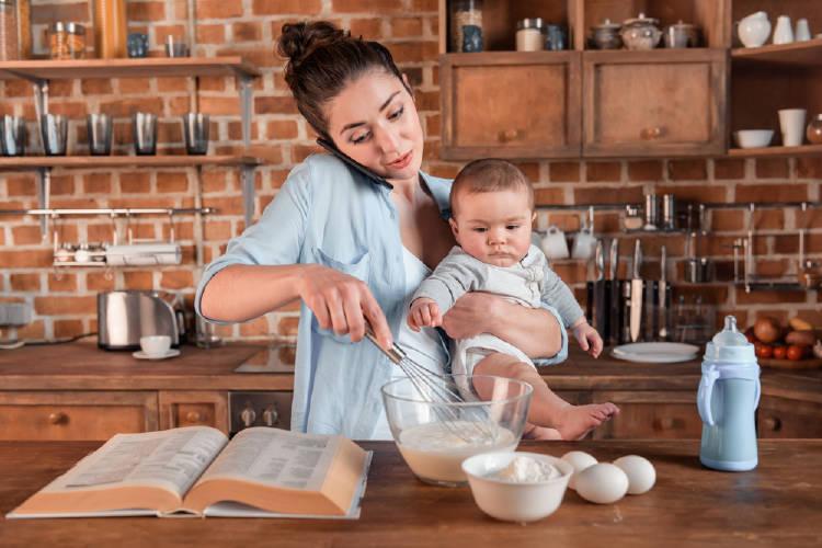 Una madre cocina con un bebé en brazos