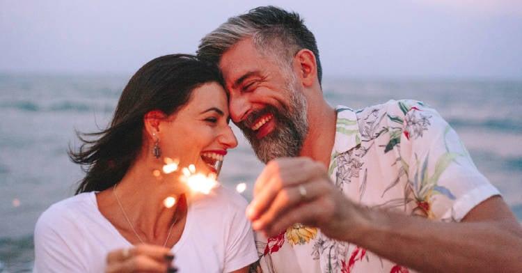 pareja feliz festejando año nuevo en la playa