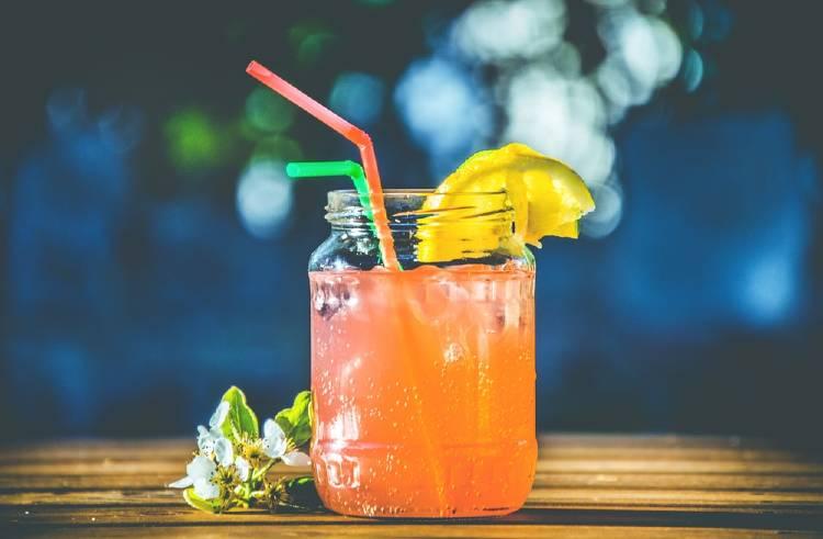 Bebida servida en un frasco de vidrio con dos sorbetes