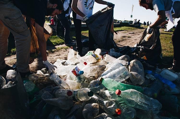 Voluntarios guardan botellas en bolsas de residuos