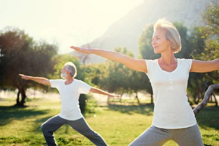 hombre y mujer de mediana edad practican yoga en parque