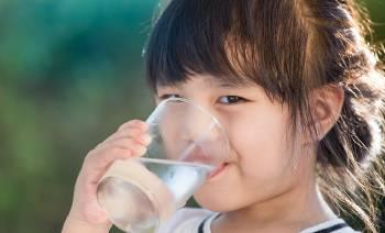 Una niña bebe un vaso de agua