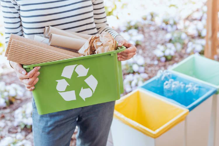Manos sosteniendo una caja con residuos para reciclar