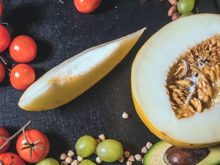 Un melón cortado al medio con otras frutas y vegetales al rededor