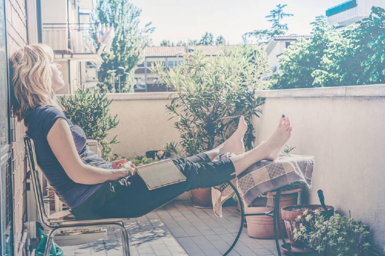 Mujer sentada en un balcón con plantas y un libro sobre sus piernas