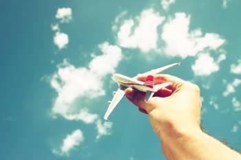 Avión de juguete sobre cielo con nubes