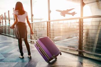 mujer con su maleta espera en el aeropuerto