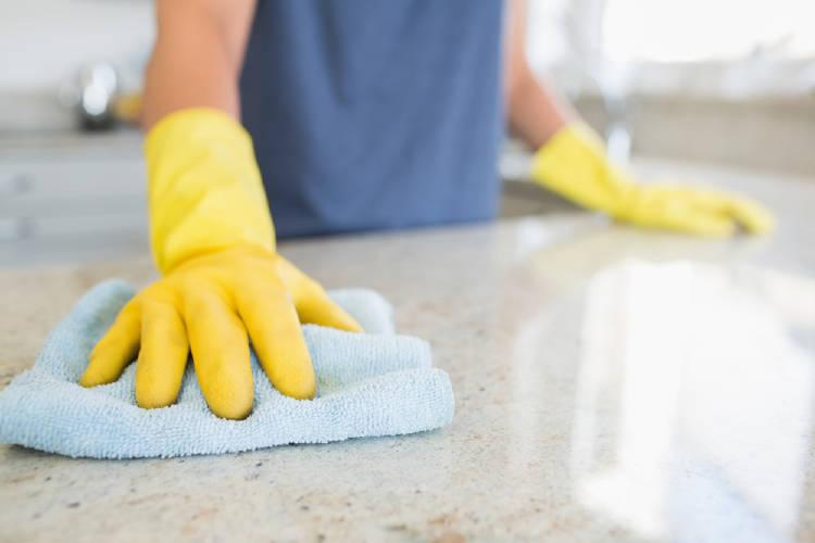 limpieza de superficie de marmol con guantes amarillos y una franela azul