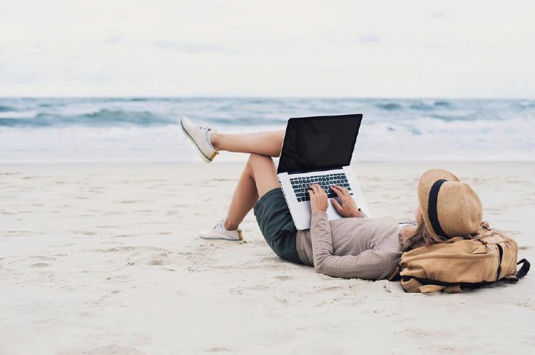 mujer computadora en la playa