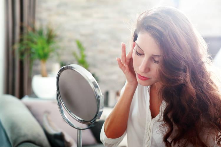 Una mujer mira su rostro en un espejo