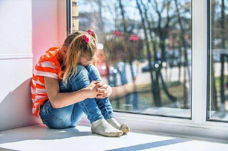 niña ansiosa frente a la ventana