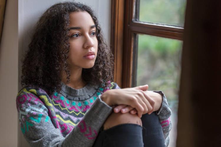 Una adolescente con expresión triste sentada al lado de una ventana
