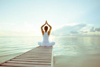 mujer practica yoga frente al mar