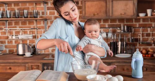 madre ama de casa cocinando con sus bebe en brazos, hablando por telefono al mismo tiempo. concepto de multitasking