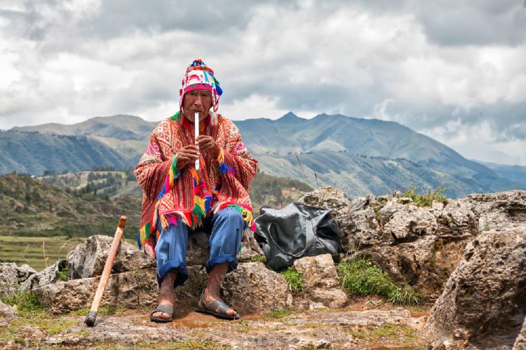 viejo sabio chaman toca un instrumento tipico en las zonas sagradas de cusco, peru