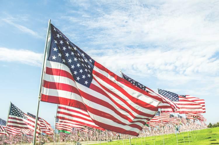 Banderas de EEUU hondeando en el viento en un campo verde