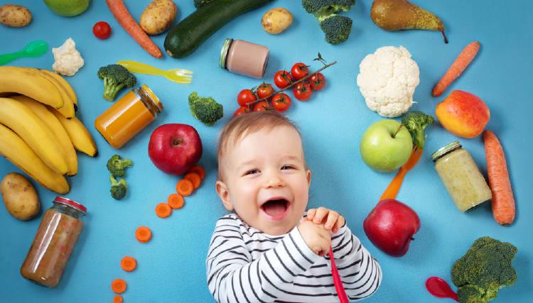 Un bebé rodeado de vegetales