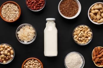 Una botella de leche con cereales y legumbres alrededor