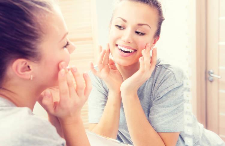 Una mujer mira la piel de su rostro en un espejo