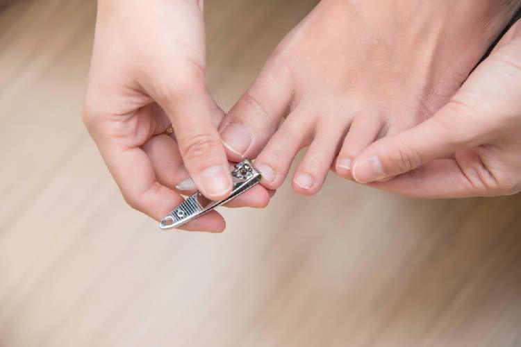 Una persona cortando las uñas de sus pies