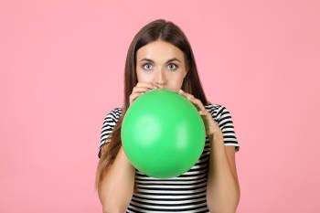 mujer infla un globo verde con su boca