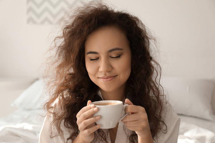 Una mujer bebe café por la mañana