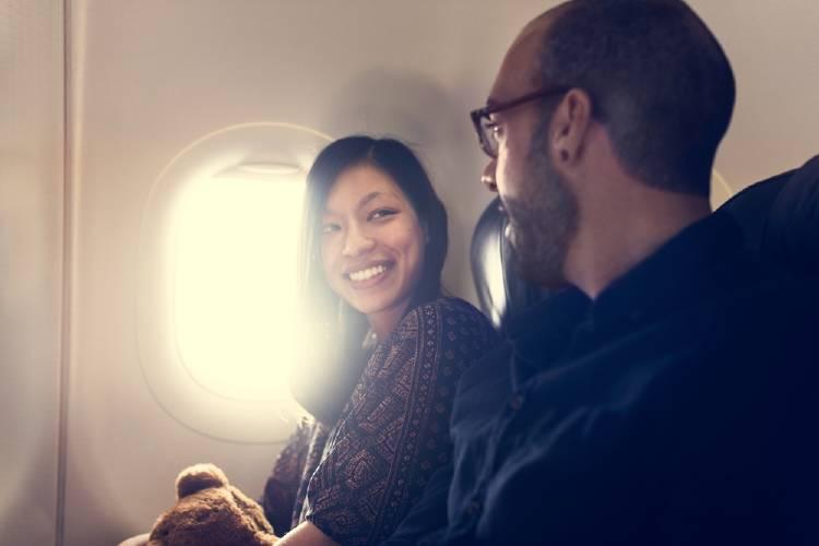 Dos pasajeros conversando en un avión