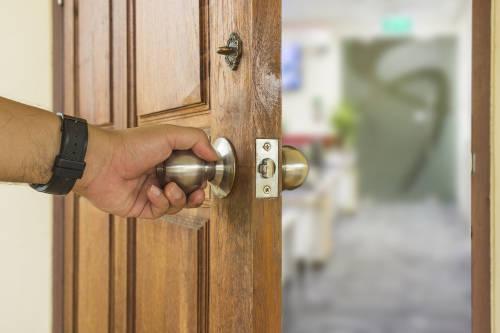 mano sostiene el picaporte para abrir una puerta de madera