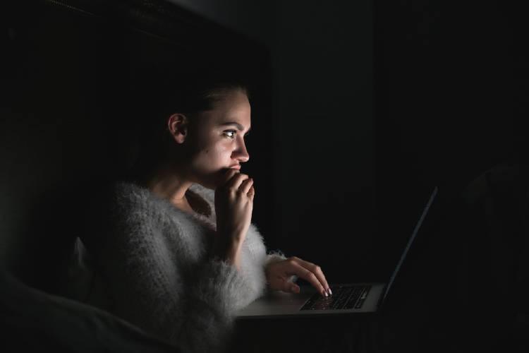 Una mujer mira la computadora de noche