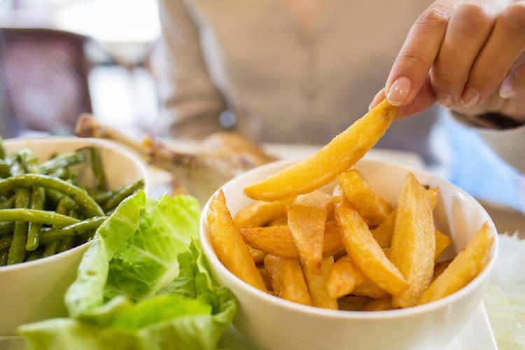 Un persona comiendo papas fritas