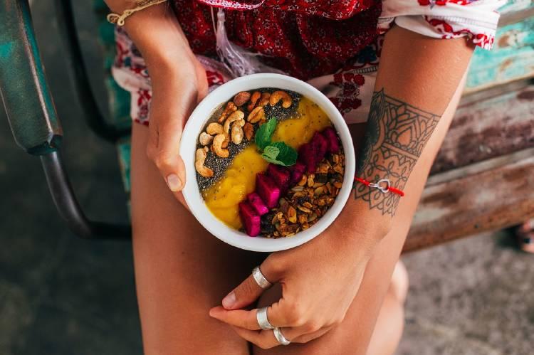 Una mujer con un bowl con frutas y frutos secos