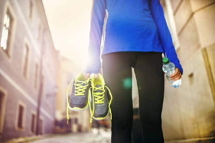 mujer sostiene botella de agua luego de hacer ejercicio