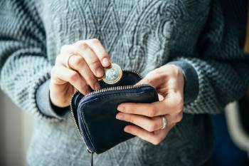 Una persona introduce monedas dentro de un monedero