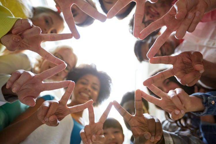 jovenes de distintas edades realizan el simbolo de la paz con sus manos en una ronda