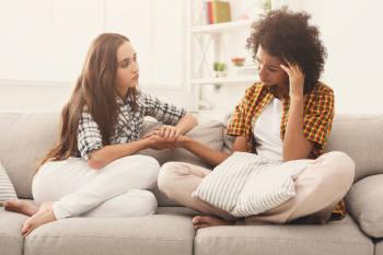 Dos mujeres conversando en un sillón, una consuela a la otra