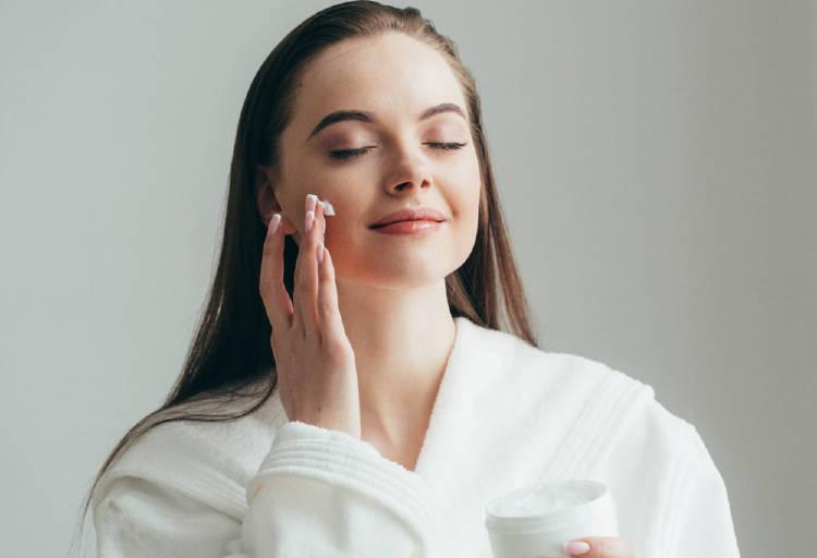 Una mujer se pone crema en el rostro