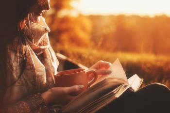 mujer disfruta de un libro y un cafe en soledad al aire libre